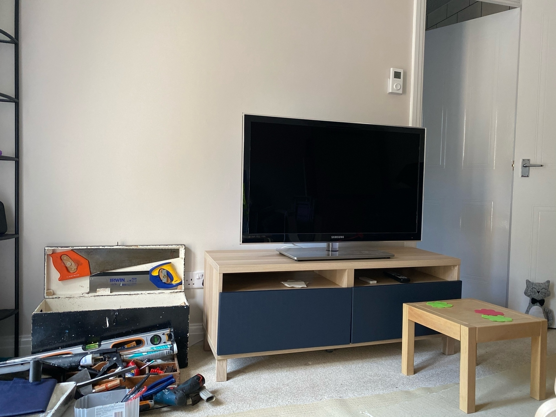 IKEA Besta TV unit with navy blue drawer fronts, TV on top. large black toolbox on the left with 2 saws in the lid.