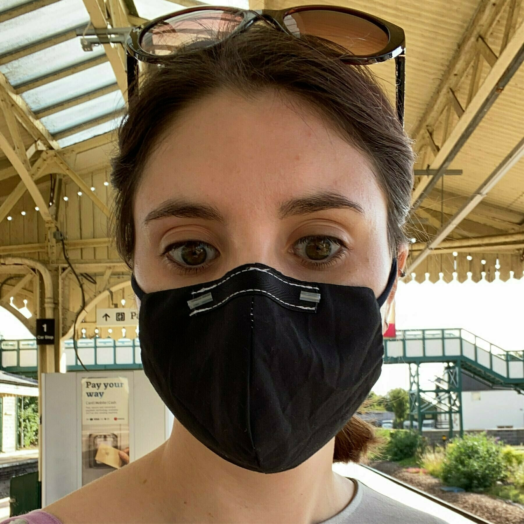Me, wearing a black fabric mask at a train station