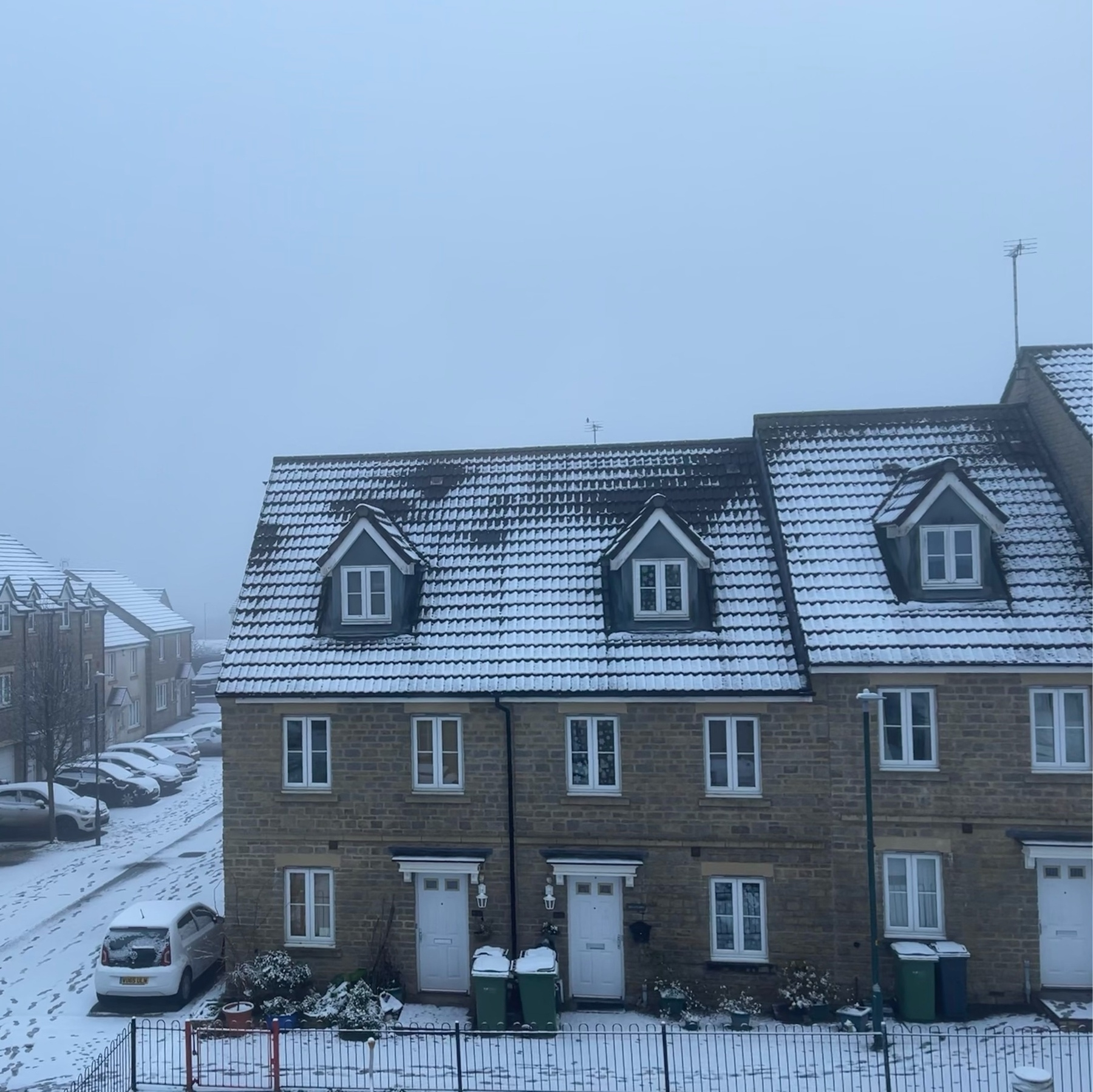 snow on the rooves of houses, cars, and the ground.
