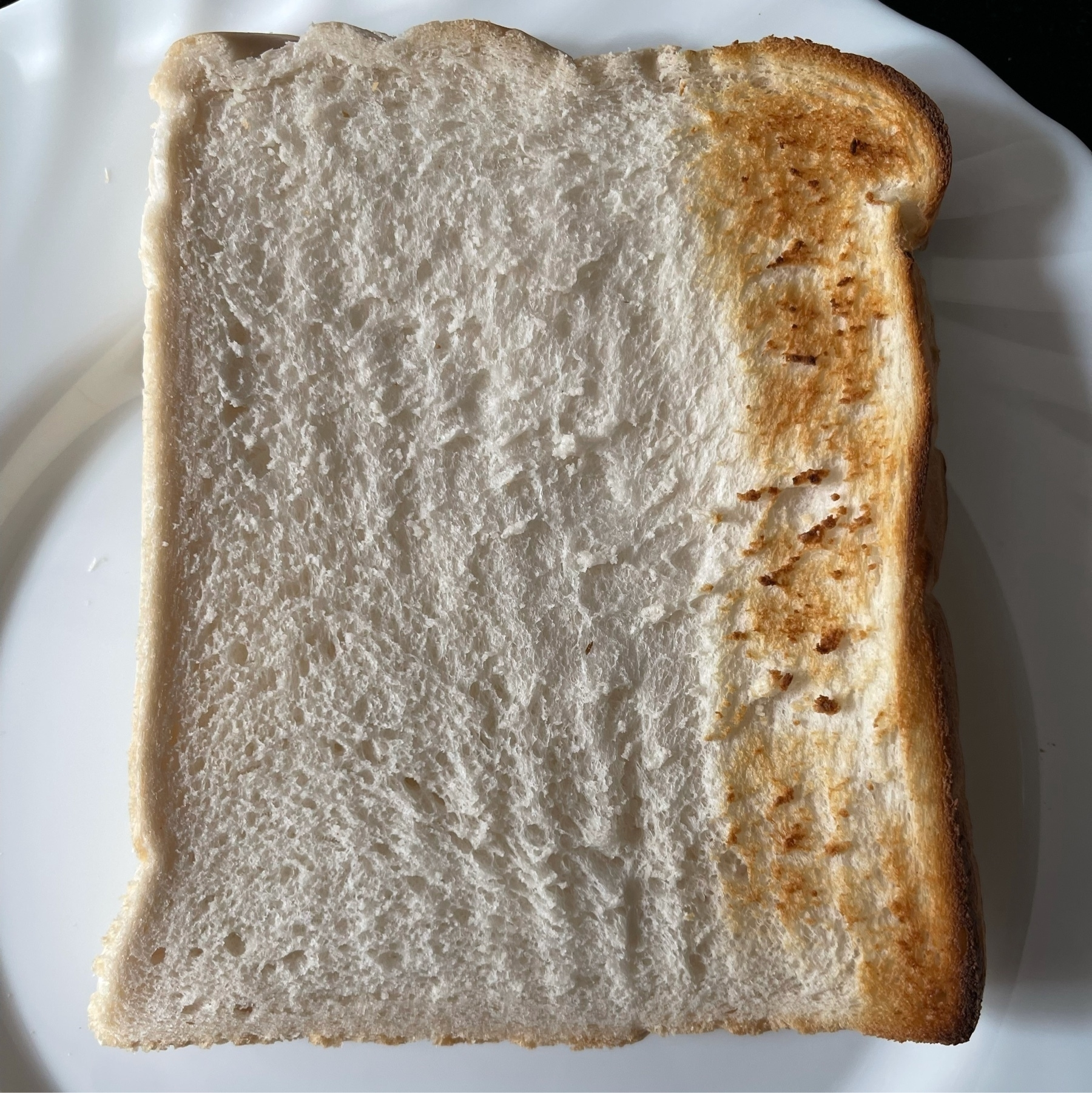Photo of a slice of bread, with a small part toasted on one side.